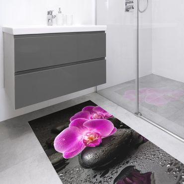 Vinyl-Teppich - Pinke Orchideenblüten auf Steinen mit Tropfen - Hochformat 1:2