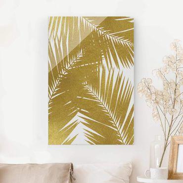 Glasbild - Blick durch goldene Palmenblätter - Hochformat