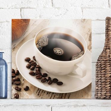 Glasbild - Dampfende Kaffeetasse mit Kaffeebohnen - Quadrat 1:1